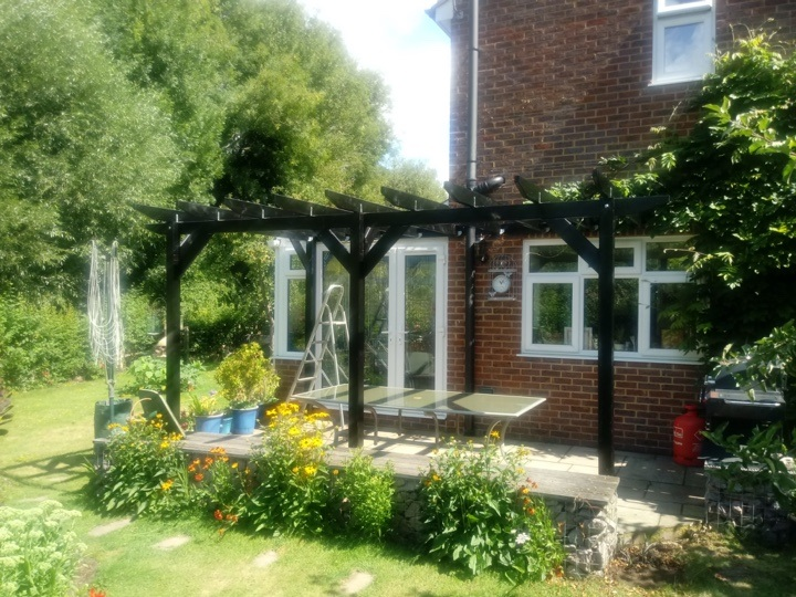 A stand alone pergola with dark stain adjacent to customer's house and conservatory